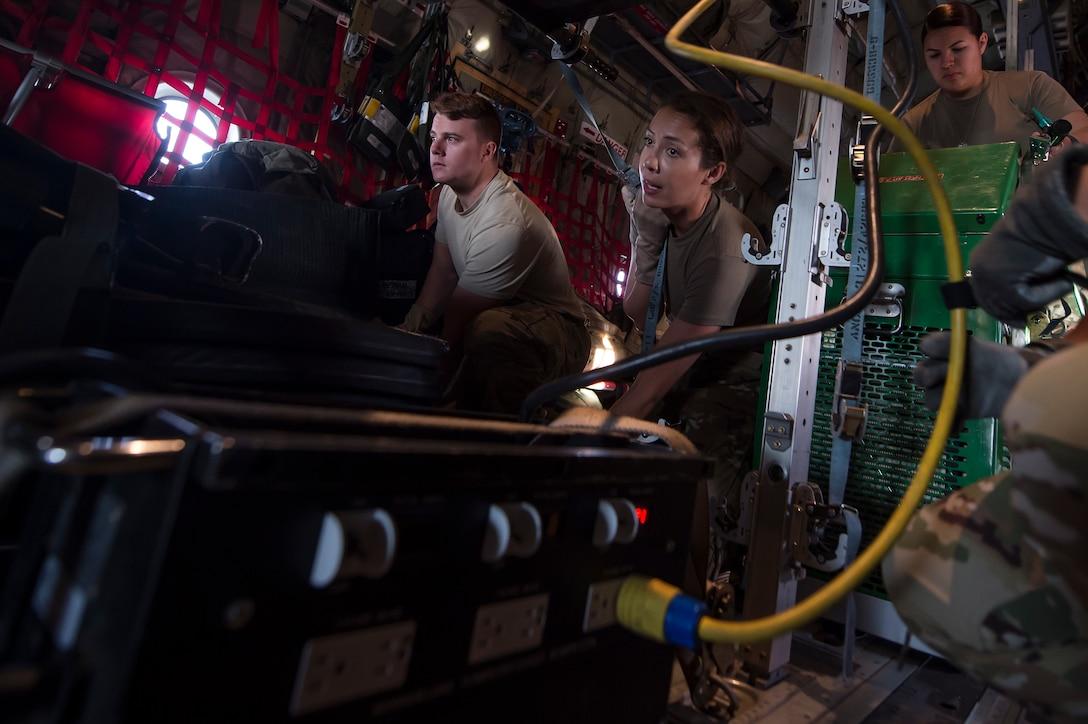 Senior Airman Robert McCabe, 379th Expeditionary Aeromedical Evacuation Squadron aeromedical evacuation technician (Left), and Capt. Aline Putnam, 379th EAES flight nurse, fasten a litter and medical equipment into place on a C-130 Hercules at Al Udeid Air Base, Qatar, before a recent aeromedical evacuation mission. (U.S. Air Force photo by Tech. Sgt. Christopher Hubenthal)