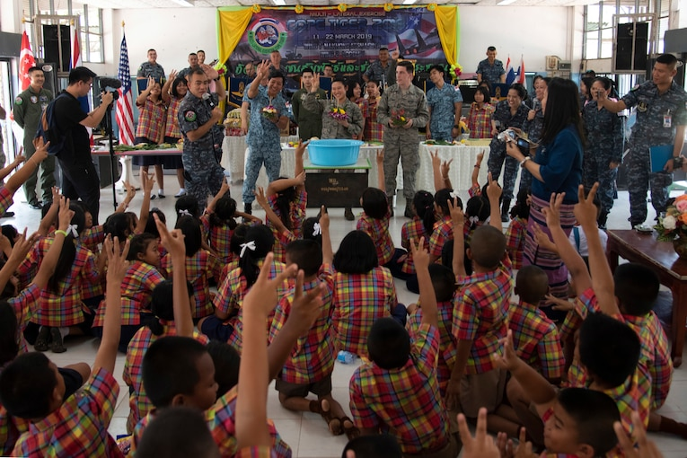 A large group of children raise their hands during a class with some military men standing in front of them.