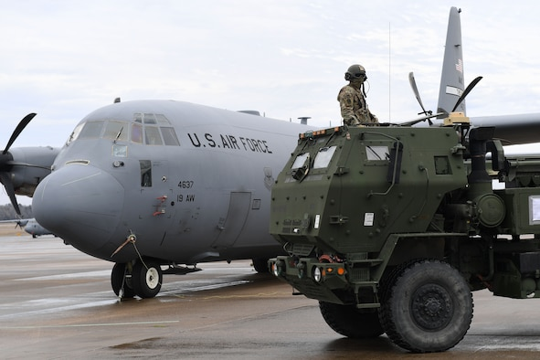 A man sits in a vehicle in front of a C-130J.