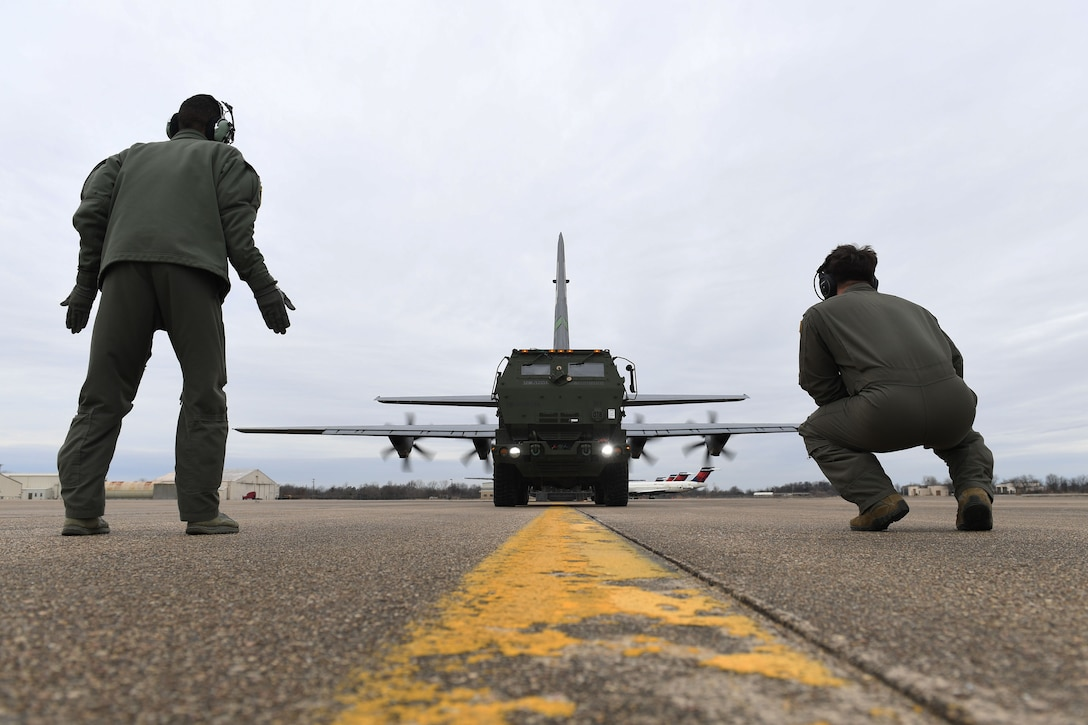 Two Airmen onload a vehicle to a C-130J.