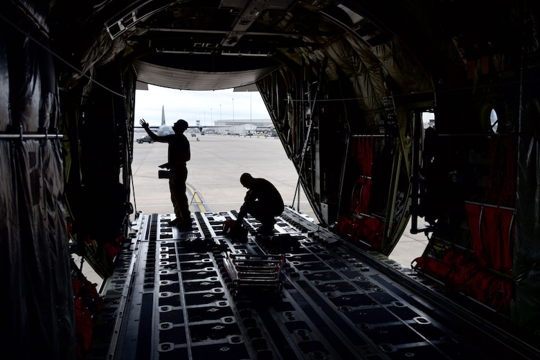 Two Airmen check the back of a C-130J.