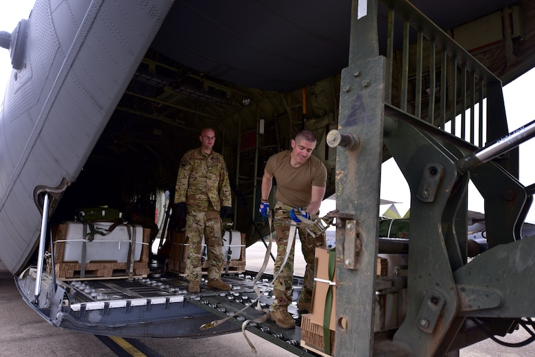 Two Airmen onload equipment to a C-130J.
