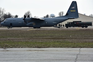 A fuel truck gets onloaded to a C-130J.