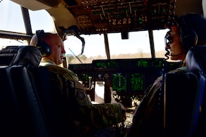 A man wearing a headset in the flight deck of a C-130J talks to another man.