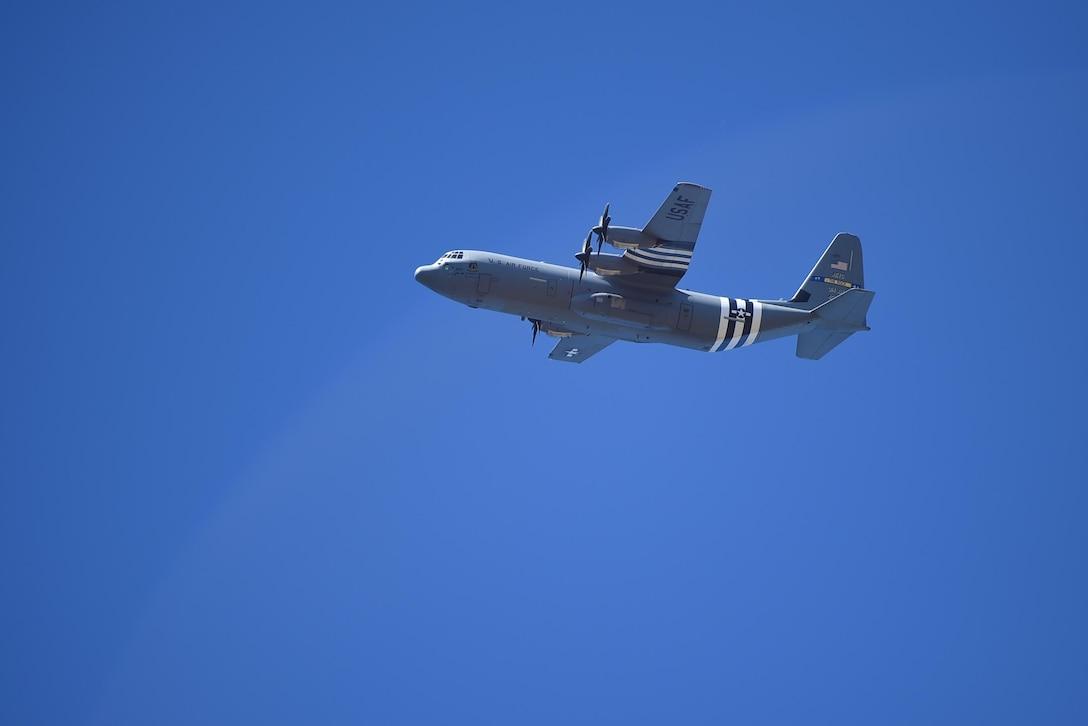 A C-130J flies overhead.