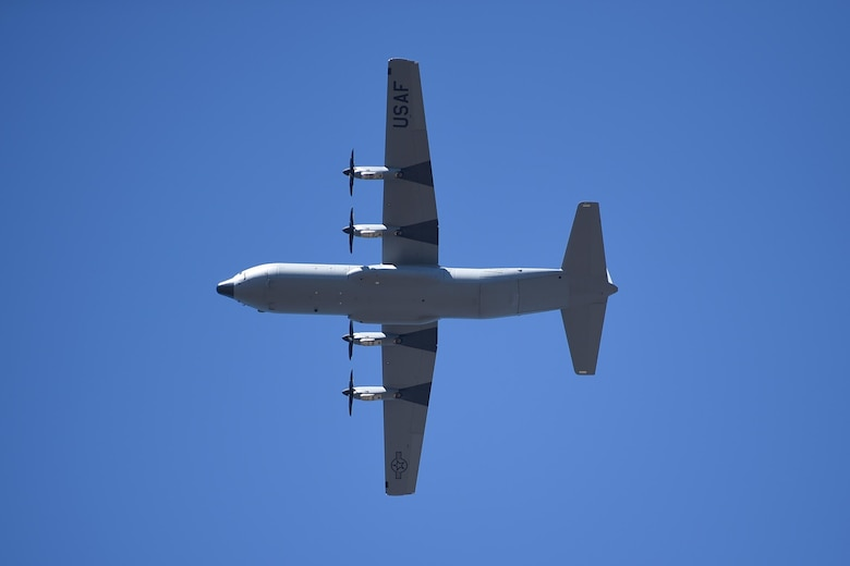 A C-130J flies overhead.