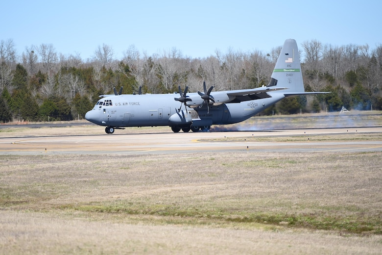 A C-130J is taxiing on a runway.