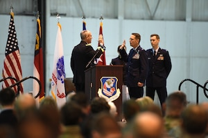 U.S. Army Maj. Gen. Gregory A. Lusk (left), the Adjutant General of North Carolina National Guard Bureau (NCNGB), swears in U.S. Air Force Col. Stephen J. Mallette (right), director of cyberspace operations for Joint Force Headquarters, NCNGB, during Col. Mallette's promotion ceremony at the North Carolina Air National Guard Base, Charlotte Douglas International Airport, Mar. 09, 2019. Family, friends, and guard members gather to watch Col. Mallette pin on the rank of Brig. Gen. He has has served for 37 years including enlisted time in the Army and Air Force.