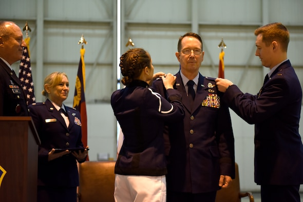 U.S. Air Force Brig. Gen. Stephen J. Mallette (middle), director of cyberspace operations for Joint Force Headquarters, North Carolina (NC) National Guard Bureau, is assisted with putting on new rank by his daughter Melanie (left), and son, 2nd Lt. Phillip Mallette, during his promotion ceremony at the NC Air National Guard Base, Charlotte Douglas International Airport, Mar. 09, 2019. Family, friends, and guard members gather to watch Col. Mallette pin on the rank of Brig. Gen. He has has served for 37 years including enlisted time in the Army and Air Force.