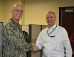 DLA Distribution Commanding Officer Navy Rear Adm. Kevin M. Jones (left) presents Glenn Mellon (right) a commander's coin during an employee recognition event Feb. 26.