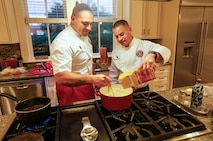Staff Sgt. Christopher Brandle, the enlisted aide for Marine Corps Recruit Depot Parris Island, guides Gunnery Sgt. Julio Aquayo while preparing a dinner for the depot's commanding general and his guests Jan. 10, 2019. As Brandle's replacement, aguayo will be responsible for the cleanliness and maintenance of the general's home, his uniforms and cooking for daily meals and events. (U.S. Marine Corps photo by Lance Cpl. Carlin Warren)