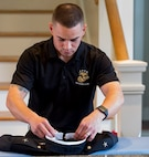 Staff Sgt. Christopher Brandle, the enlisted aide for Marine Corps Recruit Depot Parris Island, prepares Brig. Gen. James Glynn's uniforms Jan. 15, 2019. Brandle, a 29-year old from Fresno, Calif., is responsible for the cleanliness and maintenance of the general's house, his uniform and cooking for daily meals and events. (U.S. Marine Corps photo by Lance Cpl. Carlin Warren)