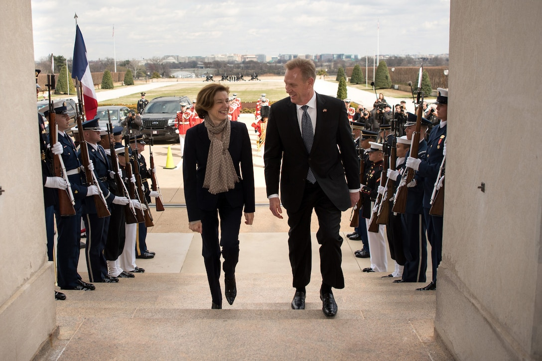 A man and a woman walk up some steps at the Pentagon.
