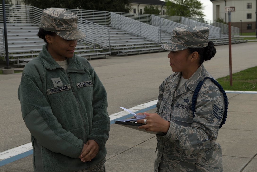 U.S. Air Force Staff Sgt. Ebone Frederick, 81st Training Support Squadron military training leader student, receives advice in performing an open-ranks inspection from Tech. Sgt. Victoria Monzon, 81st TRSS MTL instructor, at Keesler Air Force Base, Mississippi, March 15, 2019. The evaluation allowed Monzon to assist her student in performing a higher quality open-ranks inspection and strengthen the student's skill-set as a future MTL. (U.S. Air Force photo by Airman 1st Class Kimberly Mueller)
