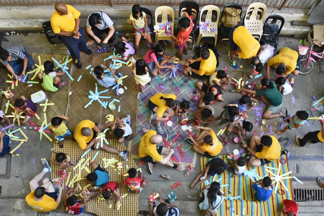An aerial view of a group of adults and children doing arts and crafts.