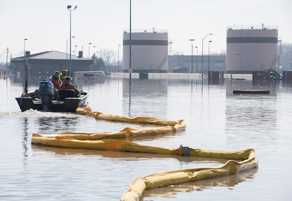 Environmental restoration employees deploy a containment boom from a boat March 18, 2019, on Offutt Air Force Base. One-third of the installation was flooded and the boom was a precautionary measure for possible fuel leaks.  (U.S. Air Force photo by Delanie Stafford)