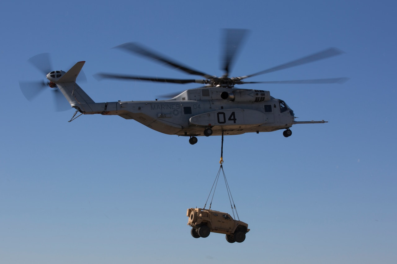 A helicopter carries a vehicle in a sling load.