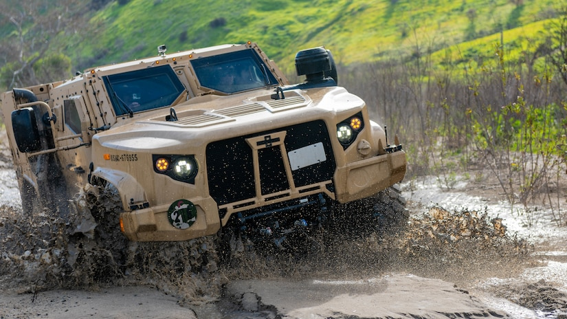 A tactical vehicle splashes through water and mud.