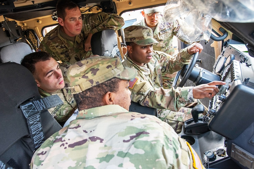 Soldiers examine touch screens inside a new military vehicle.