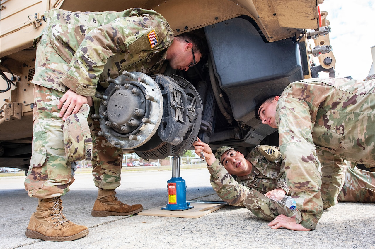 Soldiers work under a tactical vehicle.