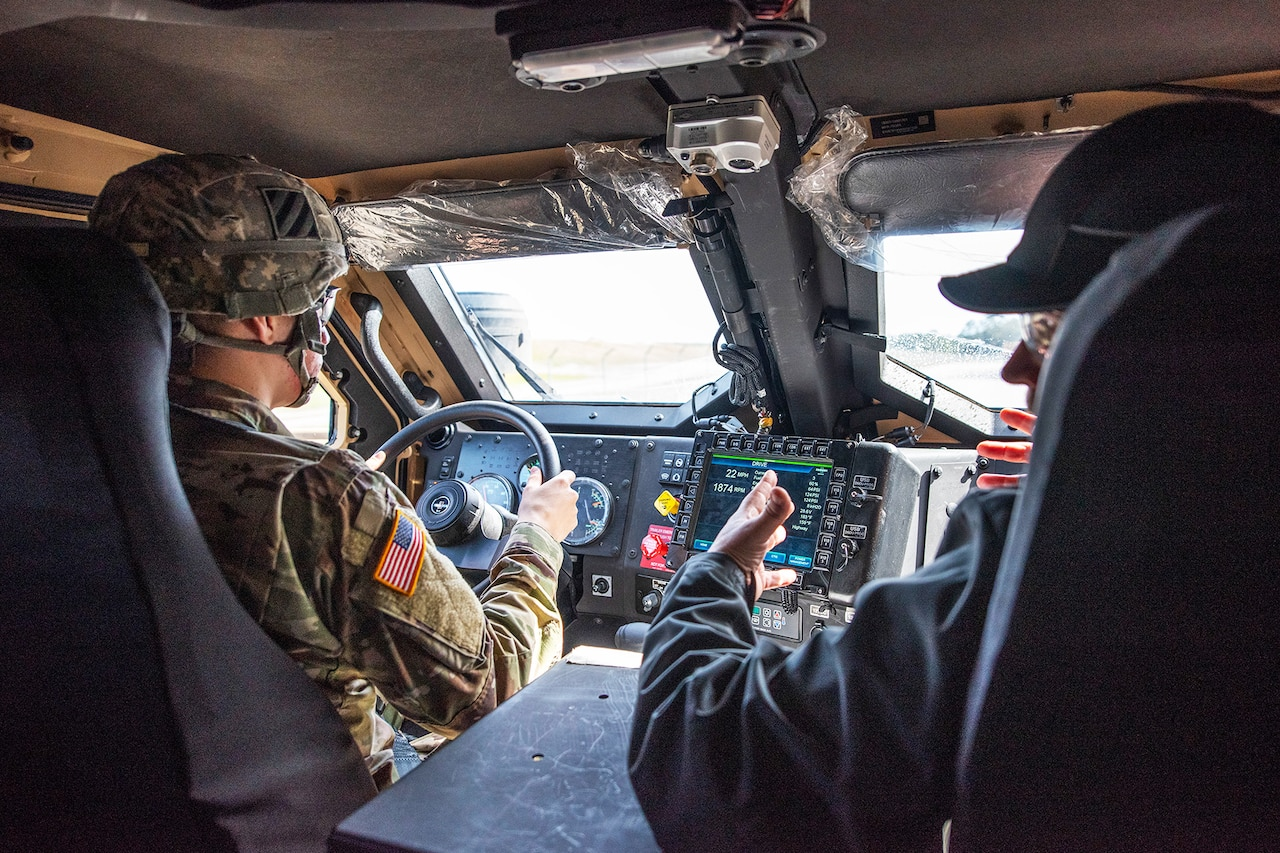 A soldier drives a new tactical vehicle as a contractor talks to rear seat passengers.