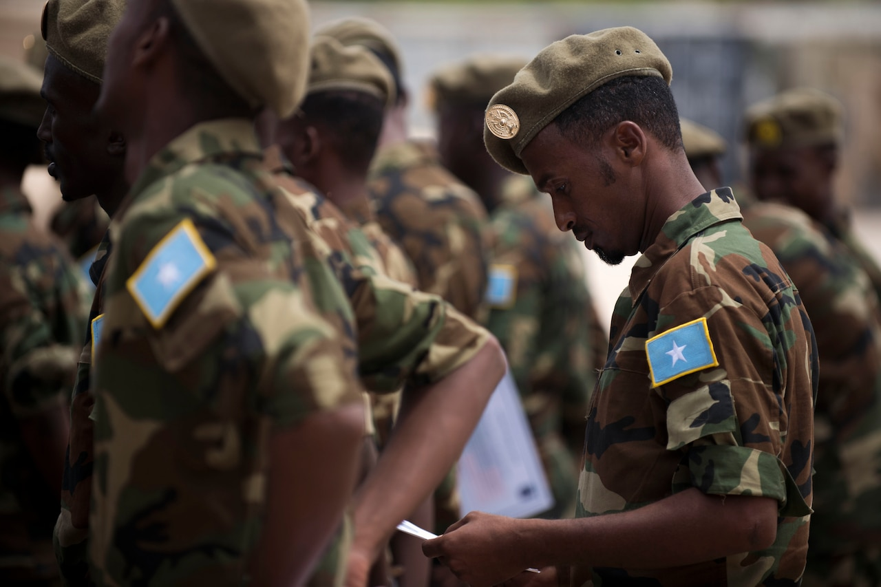 A Somali soldier in formation looks at his training certificate.