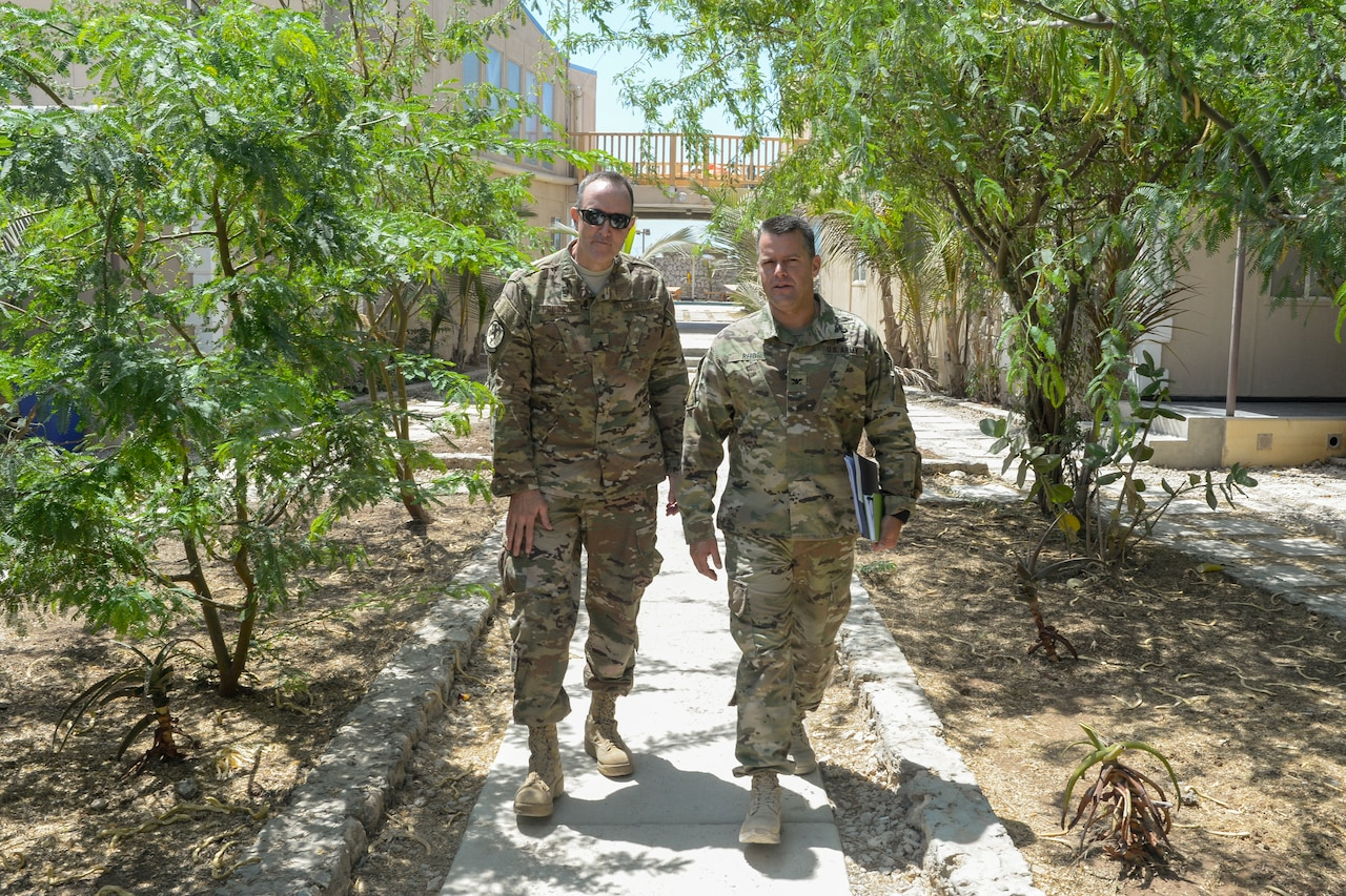 Two military officers talk while walking.