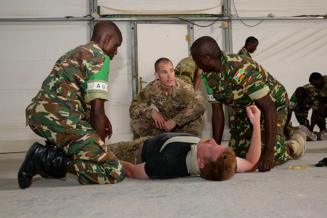 Medics kneel around a soldier lying  on the floor.