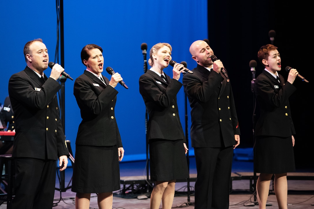 Service members sing in a chorus.