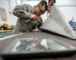 "Airman 1st Class Jose Lozada Jr., a sheet metal technician with the Massachusetts Air National Guard's 104th Fighter Wing, removes rivets to repair cracks on an F-15 Eagle tail cone in Westfield, Massachusetts, March 3, 2019. Lozada, who also has automotive body and repair jobs on the civilian side, said that even after a little more than a year of working in aircraft structural maintenance, the thrill of being around F-15s still hasn't worn off. ""Working on a jet still leaves me speechless,"" he said. ""Just to even think that I went from something so small [automobiles] to working on something so big."""