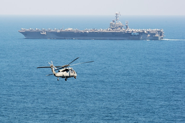 A helicopter flies toward an aircraft carrier.