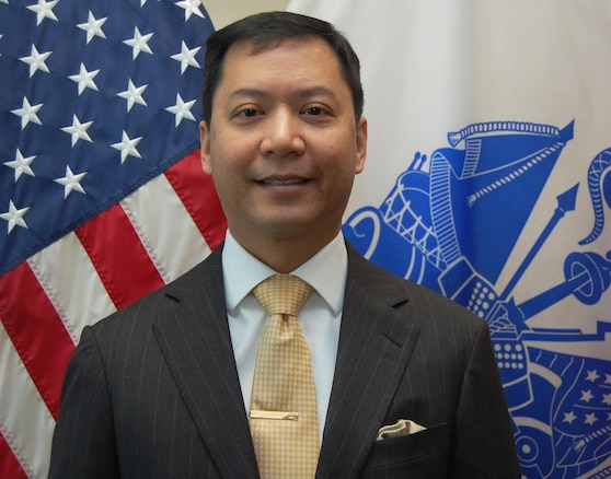 Smiling man in dark gray suit stands in front of flags