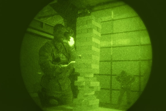 Tech. Sgt.  Jerald Harris, 50th Security Forces Squadron flight chief, challenges his motor skills by playing Jenga while using night vision goggles during a training session at the 50th SFS training facility at Schriever Air Force Base, Colorado, March 16, 2019. The 50th SFS training flight incorporated games as a way to increase training engagement and boost morale while meeting requirements.  (U.S. Air Force photo by Staff Sgt. Matthew Coleman-Foster)