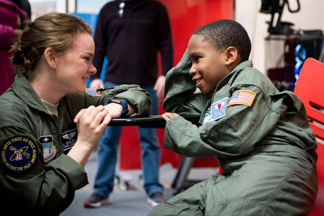 An airman speaks to a young child.