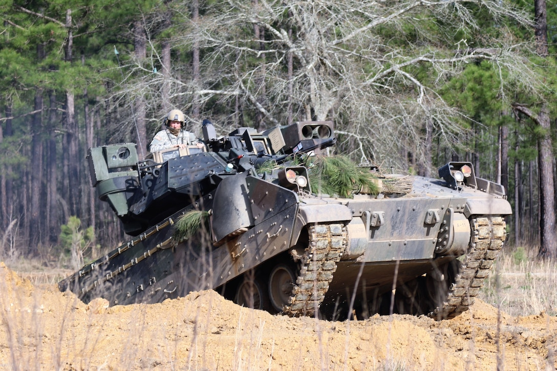 Soldiers ride in a tank as it climbs up an embankment.