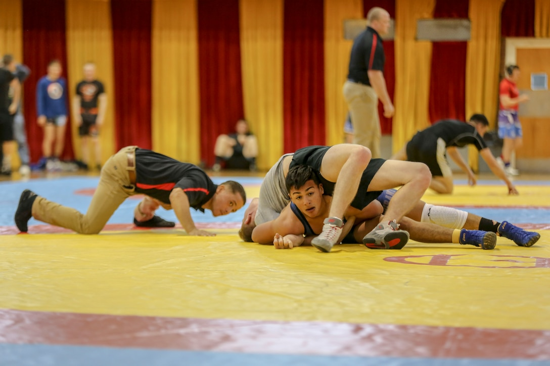 Two men wrestle each other during a tournament as a third man watches.