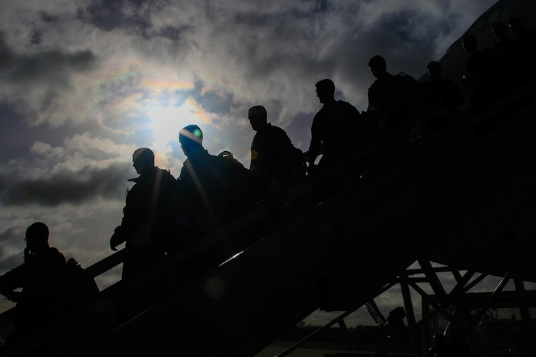 Service members walk off a plane.