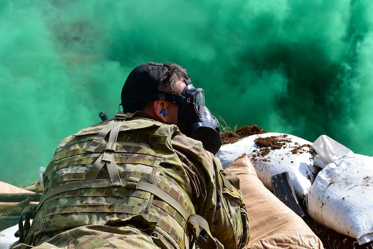 A soldier wearing a gas mask lies behind a haze of green smoke.