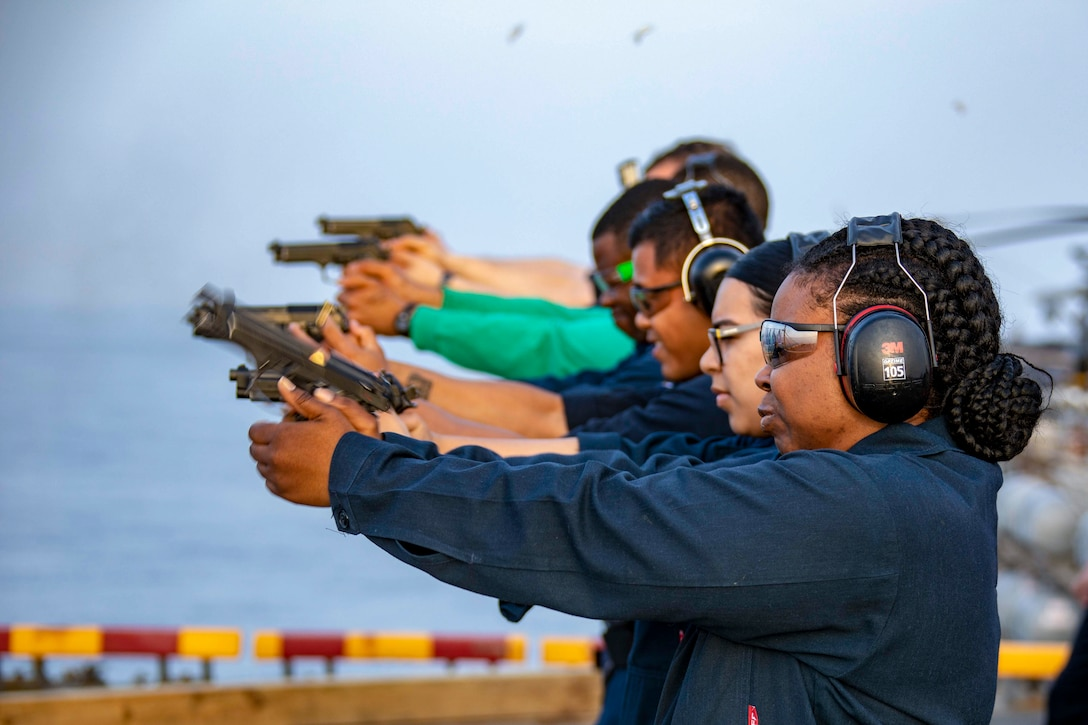 A group of sailors standing in a row fire guns.