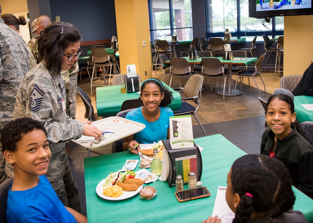 Senior Master Sgt. Regina Dockens, 23d Civil Engineer Squadron first sergeant, serves food to participants during a deployed spouse's dinner, March 19, 2019, at Moody Air Force Base, Ga. The mission's success depends on resilient Airmen and families, who are prepared to make sacrifices with the support of their fellow Airmen, local communities and leadership. (U.S. Air Force photo by Airman 1st Class Eugene Oliver)