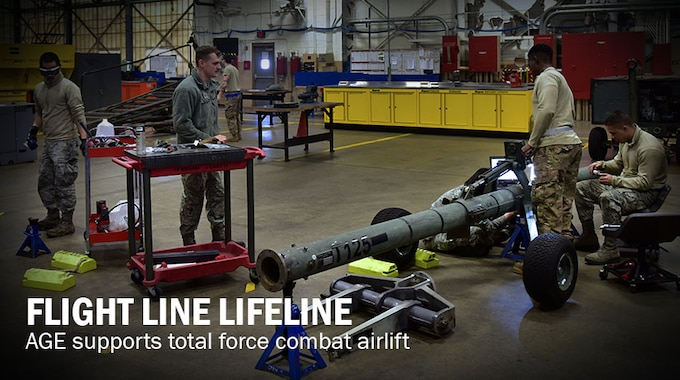 four airmen work on a variety of mechanical items in a workshop.