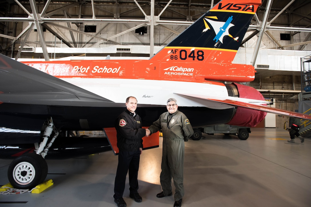 Col. Ryan Blake, U.S. Air Force Test Pilot School commandant (left), poses for a photo with aviation artist Mike Machat in front of the school's NF-16D VISTA in-flight simulator March 7. The VISTA is sporting a new paint scheme designed by Machat. 