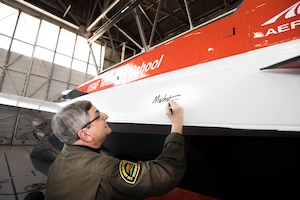 Renowned aviation artist Mike Machat officially endorsed his latest work for the U.S. Air Force Test Pilot School March 7 when he applied his signature to the school's NF-16D VISTA in-flight simulator. (U.S. Air Force photo by Joe Jones)