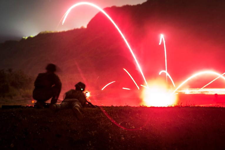Two Marines fire their weapons causing tracers in a red sky.
