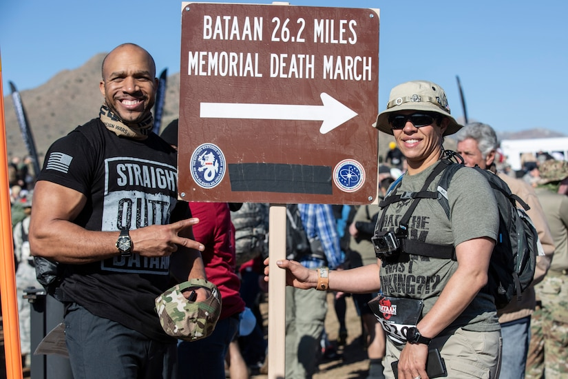 "A man and woman pose for a photo with a sign reading ""Bataan 26.2 Memorial Death March."""