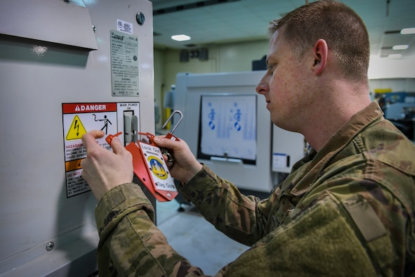 Tech. Sgt. Michael Howard, safety representative with the 911th Maintenance Squadron Metals Technology Shop, locks a piece of equipment at its power source while learning the machine's safety procedures at March Air Reserve Base, California, March 5, 2019. The machine is similar to the equipment the 911th MXS will be receiving at their home station and learning the safety precautions is a priority requirement for working with them. (U.S. Air Force photo by Joshua J. Seybert)