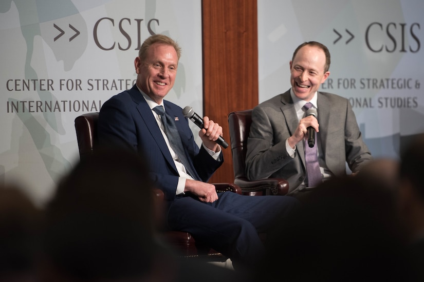 Acting Defense Secretary Patrick M. Shanahan sits on a stage holding a microphone next to another man sitting on stage holding a microphone.