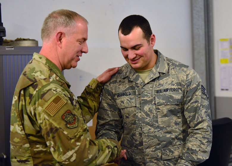 U.S. Air Force Maj. Gen. John Gordy, U.S. Air Force Expeditionary Center commander, hands a coin to Staff Sgt. Cody Griswold, 721 Aircraft Maintenance Squadron vehicle noncommissioned officer, for outstanding performance in his unit at Ramstein Air Base, Germany, March 14, 2019.