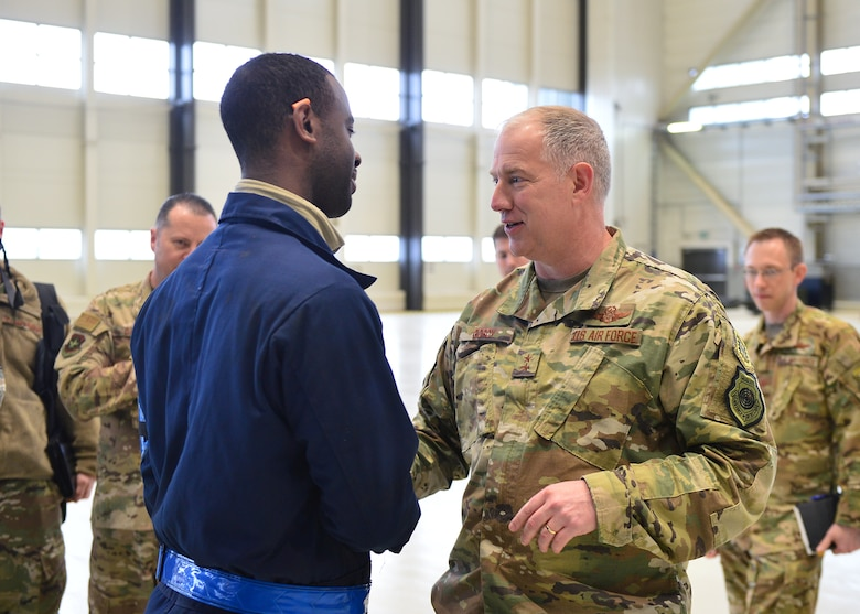 U.S. Air Force Maj. Gen. John Gordy, U.S. Air Force Expeditionary Center commander, hands a coin to Staff Sgt. Reuben Bowers, 721 Aircraft Maintenance Squadron C-17 Globemaster crew chief craftsman, for outstanding performance in his unit at Ramstein Air Base, Germany, March 14, 2019.