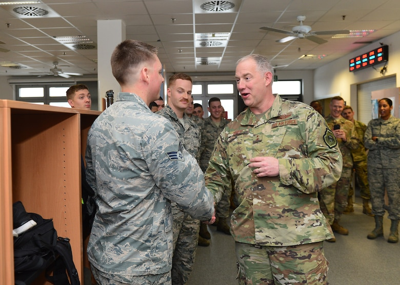 U.S. Air Force Maj. Gen. John Gordy, U.S. Air Force Expeditionary Center commander, hands a coin to Senior Airman Taylor Eide, 721 Aircraft Maintenance Squadron hydraulic journeyman, for outstanding performance in his unit at Ramstein Air Base, Germany, March 14, 2019.